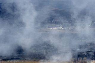 Периодически дым рассеивается и становится виден город