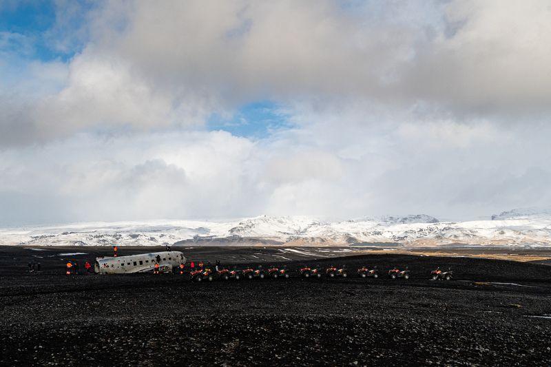 ATV; DC plane; Iceland; Vík; Vík í Mýrdal; climbing; clouds; landscape; light; nature; people; plane; sky; snow; stones; travel; winter; wreck;  The Abandoned DC Plane on Sólheimasandur and line of ATVsphoto preview
