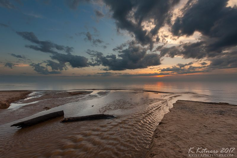 sea seascape river water sky clouds branch coast beach sand sunset evening latvia At The Seaphoto preview