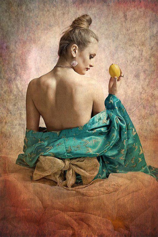 Девушка сидящая на коленях с лимоном в правой рукеphoto preview