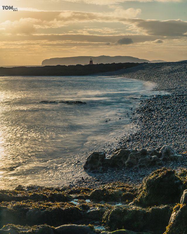 sea motion uk england water blue sunset waves sun lighthouse stone rocks rock green blue yellow clouds cloud sky  \