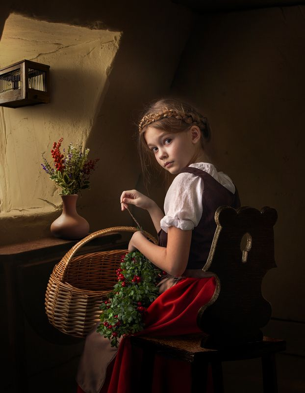 Young girl weaves a wreath at the windowphoto preview